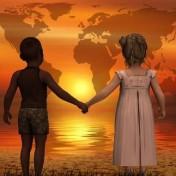 678-381-kinder-stehen-in-der-Abendsonne-in-Verbundenheit-Hand-in-Hand-am-Ufer-und-schauen-in-Liebe-auf-die-Welt-678x381